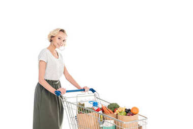 attractive young woman standing with shopping trolley and smiling at camera isolated on white