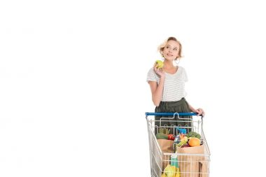 smiling young woman holding apple and looking away while standing with shopping trolley with grocery bags isolated on white