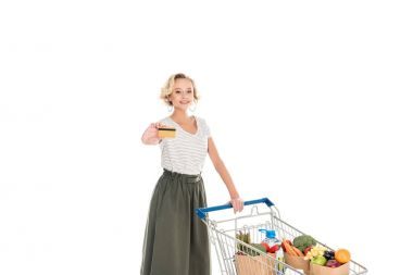 woman holding credit card and smiling at camera while standing with shopping trolley full of grocery isolated on white