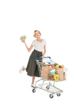 happy young woman holding dollar banknotes and standing with shopping trolley full of grocery isolated on white