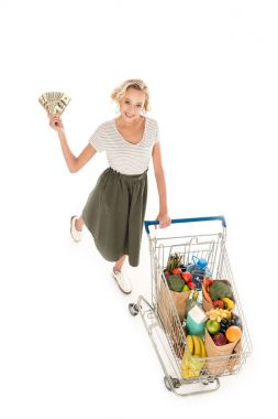 high angle view of young woman holding dollar banknotes and smiling at camera while standing with shopping trolley full of grocery isolated on white