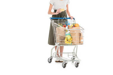 cropped shot of woman holding credit card while standing with shopping trolley full of grocery isolated on white
