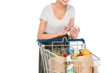 cropped shot of young woman using smartphone while leaning at shopping trolley with grocery bags isolated on white