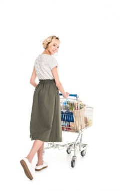 beautiful young woman smiling at camera while pushing shopping trolley with grocery bags isolated on white