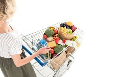 cropped shot of woman holding credit card and shopping trolley with grocery bags isolated on white