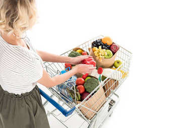 cropped shot of woman standing with shopping trolley full of grocery isolated on white