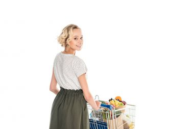 beautiful girl smiling at camera while pushing shopping trolley with grocery bags and plastic bottle of water isolated on white