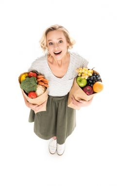 high angle view of cheerful young woman smiling at camera while standing with paper bags full of fresh fruits and vegetables isolated on white