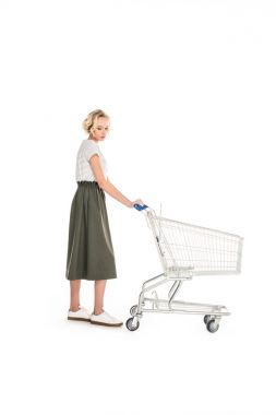 full length view of upset young woman standing with empty shopping cart isolated on white