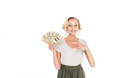beautiful smiling young woman holding dollar banknotes and pointing with finger isolated on white