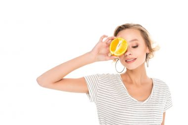 attractive young woman holding half of orange near face isolated on white