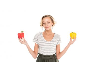 portrait of woman holding fresh bell peppers in hands isolated on white