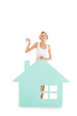 Young woman with keys in hand standing near house model isolated on white stock vector