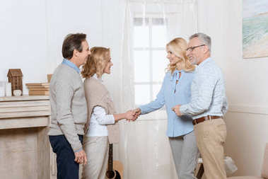 Couple of middle aged man and woman greeting their friends as guests and shaking hands