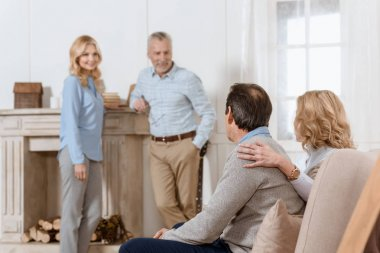 Adult men and women having friendly conversation in living room