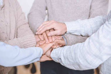 Close-up view of men and women stacking hands together