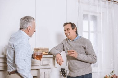 Two men with glasses in hands speaking near wall in room