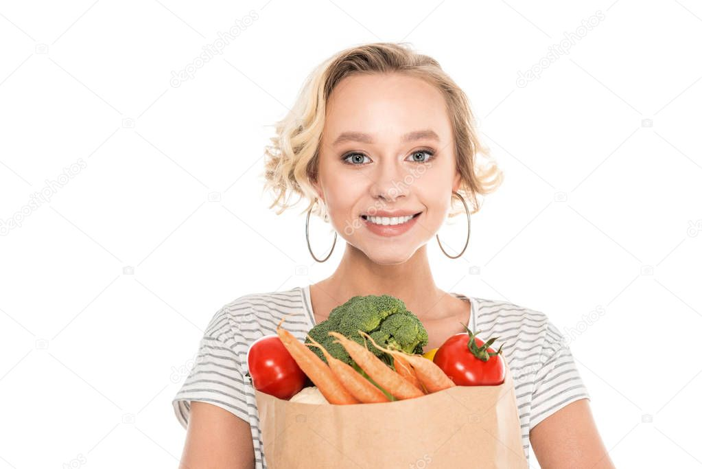 beautiful young woman holding grocery bag and looking at camera isolated on white