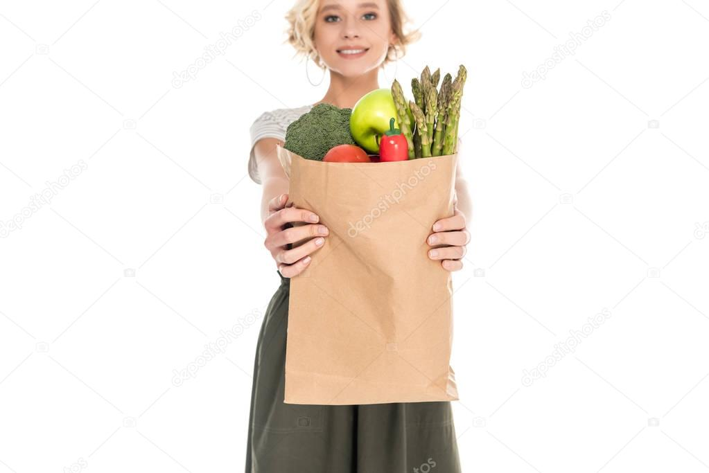 beautiful young woman holding grocery bag and smiling at camera isolated on white