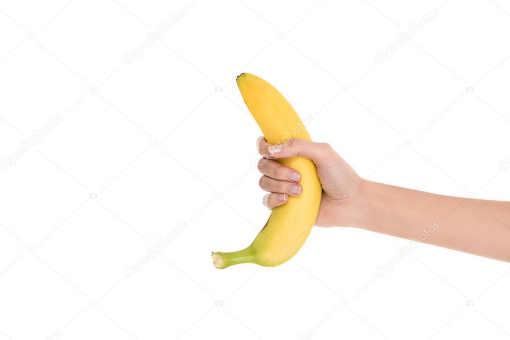 cropped shot of woman holding fresh banana in hand isolated on white
