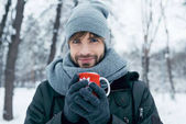 Photo young man holding cup of hot coffee in hands in winter park