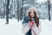 portrét krásné mladé ženy s šálkem horké kávy v ruce v zasněženém parku