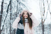 Fotografie portrét usmívající se žena v zimním oblečení při pohledu na fotoaparát v zasněženém parku