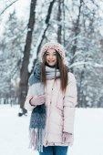 Porträt einer lächelnden Frau in Winterkleidung, die im verschneiten Park in die Kamera blickt