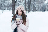 portrait of attractive woman in winter clothing with coffee to go on winter day in park