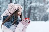 boční pohled na krásné mladé ženy s šálkem horké kávy v ruce v zasněženém parku