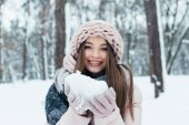 portrait of cheerful woman in winter clothing with snow in hands in park