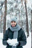 portrét šťastný mladý muž si hraje s sníh v zimě parku