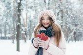 portrét krásné mladé ženy s srdce v rukou při pohledu na fotoaparát v zasněženém parku