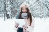 portrét usměvavé mladé ženy s tablet v zimě parku