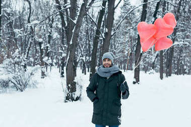 portrait of young smiling man with heart shaped balloons in winter park