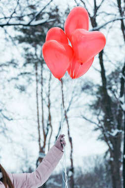 cropped shot of woman holding heart shaped balloons in hand