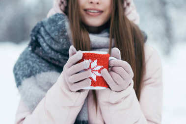 selective focus of woman with cup of hot coffee in hands in snowy park