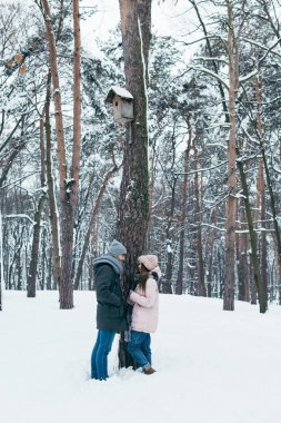 young couple looking at each other while standing in winter forest