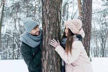 cheerful young couple standing at tree in winter park