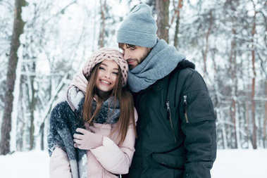 young man hugging girlfriend in winter forest