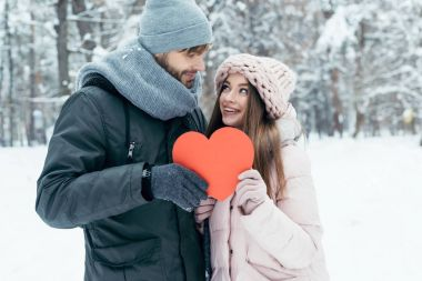 Portrait of young couple holding red heart in hands together in winter park stock vector