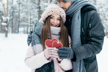 tender couple with red hearts in snowy park on winter day