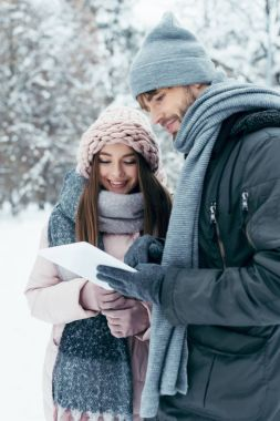 portrait of young happy couple with tablet in snowy park