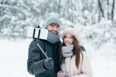 selective focus of smiling couple taking selfie together on smartphone in winter park