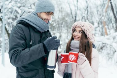 young couple drinking tea from thermos in winter park