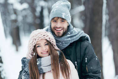 portrait of happy couple looking at camera in snowy park