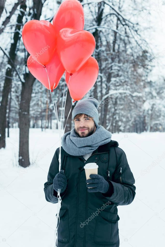 portrait of young man with coffee to go and heart shaped balloons in winter park