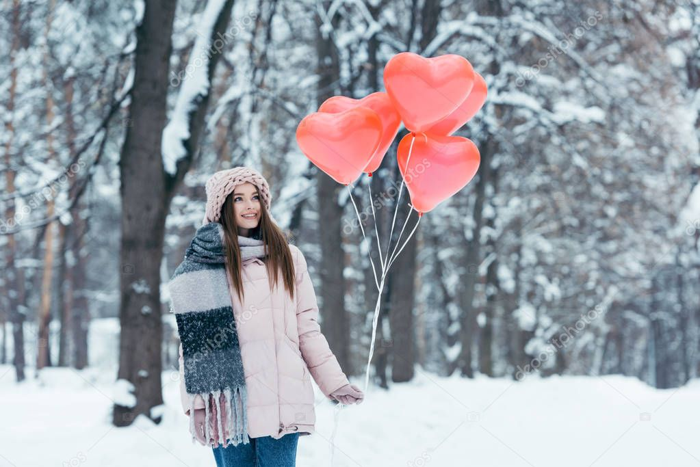 portrait of beautiful young girl with heart shaped balloons in winter park