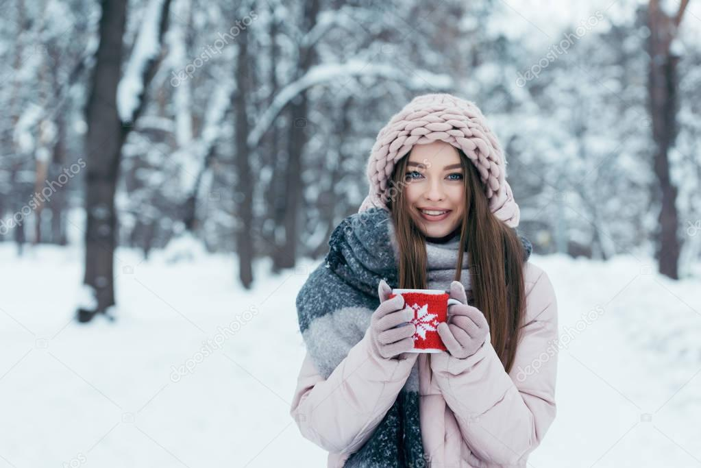 portrait of beautiful young woman with cup of hot coffee in hands in snowy park