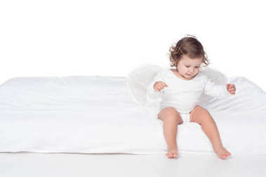 adorable happy baby with wings sitting on bed, isolated on white